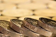 Monedas de libra británica en un fondo de más dinero foto de archivo
