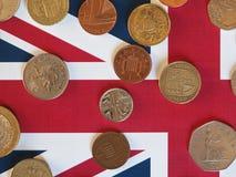 Monedas de libra, Reino Unido sobre bandera Imagenes de archivo