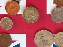 Monedas de libra, Reino Unido sobre bandera Fotografía de archivo