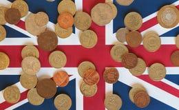 Monedas de libra, Reino Unido sobre bandera Foto de archivo