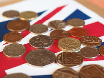 Monedas de libra, Reino Unido sobre bandera Imagen de archivo libre de regalías
