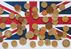 Monedas de libra, Reino Unido sobre bandera Imagen de archivo