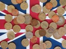 Monedas de libra, Reino Unido sobre bandera Fotos de archivo