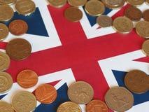 Monedas de libra, Reino Unido sobre bandera Fotos de archivo libres de regalías
