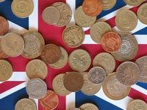 Monedas de libra, Reino Unido sobre bandera Fotografía de archivo libre de regalías