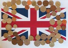 Monedas de libra, Reino Unido sobre bandera Imágenes de archivo libres de regalías