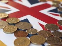 Monedas de libra, Reino Unido sobre bandera Foto de archivo libre de regalías