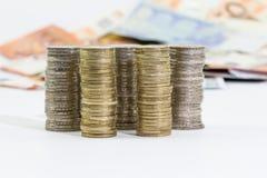 Monedas de los billetes de banco apilados y euro de los euros 2 y 1 Fotografía de archivo libre de regalías