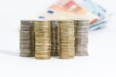 Monedas de los billetes de banco apilados y euro de los euros 2 y 1 Imágenes de archivo libres de regalías