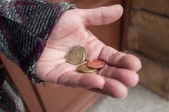 Monedas de los euros a disposición de la mujer pobre Fotografía de archivo libre de regalías