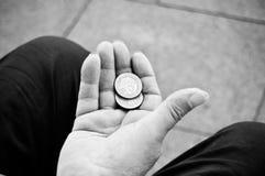 Monedas de los euros a disposición del pobre hombre Foto de archivo