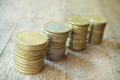 Monedas de los euros y de los centavos en fondo de madera Fotos de archivo