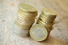 Monedas de los euros y de los centavos en fondo de madera Imagen de archivo