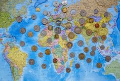 Monedas de los países diferentes en el fondo del mapa del mundo Imagen de archivo libre de regalías