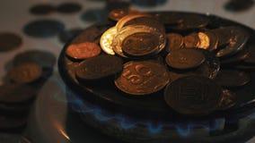 Monedas de los pa?ses diferentes en un mechero de gas S?mbolo de los precios de combustible cada vez mayores metrajes