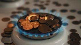 Monedas de los pa?ses diferentes en un mechero de gas S?mbolo de los precios de combustible cada vez mayores almacen de video