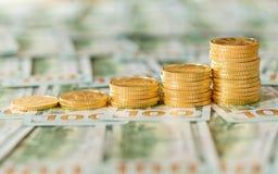 Monedas de oro apiladas en nuevos billetes de dólar del diseño $100 Fotografía de archivo libre de regalías