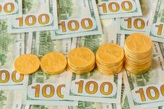 Monedas de oro apiladas en nuevos billetes de dólar del diseño 100 Foto de archivo