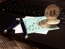 Monedas de oro de Bitcoin en el teclado del ordenador portátil Nota del negocio bajo la forma de gráfico Fotografía de archivo