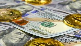 Monedas de oro de bitcoins y un fondo de las cuentas del ciento-dólar El concepto de operaciones financieras Economía del metrajes