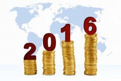 Monedas de oro con el mapa y los números 2016 Foto de archivo libre de regalías