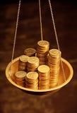Monedas de oro en balanzas  Foto de archivo libre de regalías