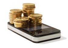 Monedas de oro en el teléfono móvil celular Imagenes de archivo
