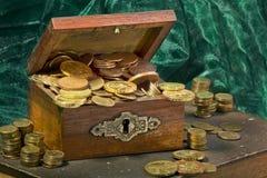 Monedas de oro en un ataúd Foto de archivo