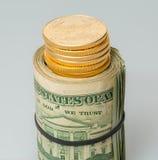 Rollo de $20 billetes de dólar con las monedas de oro Imagen de archivo libre de regalías