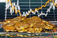 Monedas de oro y carta financiera como fondo fotos de archivo