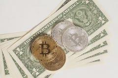 Monedas de oro y de plata del bitcoin y billetes de banco de un dólar Foto de archivo libre de regalías