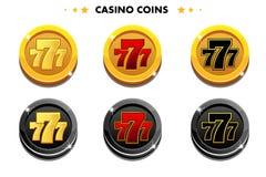 Monedas de oro y negras 777, símbolos del juego del casino Foto de archivo