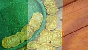 Monedas de oro y sombrero verde en una tabla con una bandera irlandesa en el primero plano