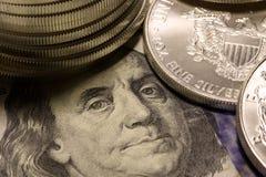 Monedas de plata encima de cientos billetes de dólar Imagenes de archivo