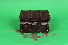 Monedas de plata que se derraman fuera de cofre del tesoro de madera Fotos de archivo