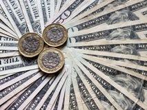 monedas de un libra y fondo esterlinas con las cuentas de dólares americanas