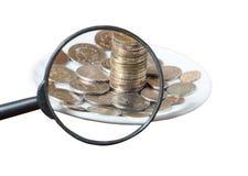 Monedas debajo de una lupa aislada Imagenes de archivo