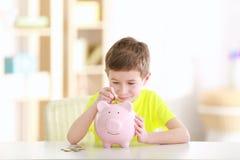Monedas del ahorro del niño pequeño en la hucha Fotos de archivo libres de regalías