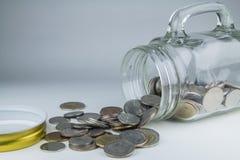 Monedas del baht tailandés que se derraman fuera del tarro del dinero Fotos de archivo