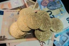 Monedas del bitcoin en notas del dólar Fotos de archivo