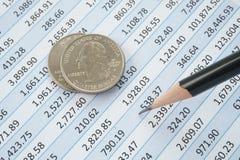Monedas del dólar cuarto encima de la hoja de cálculo Foto de archivo libre de regalías