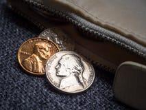 Monedas del dólar de EE. UU. colocadas fuera de la cartera Imágenes de archivo libres de regalías