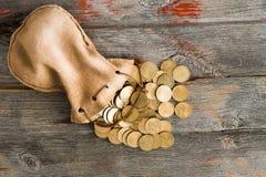 Monedas del dólar que se derraman fuera de una bolsa del lazo Imagen de archivo libre de regalías