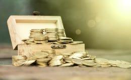 Monedas del dinero en una caja de madera Foto de archivo libre de regalías
