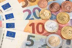 Monedas del euro y del centavo en billetes de banco Foto de archivo libre de regalías