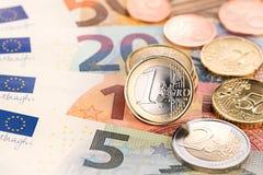 Monedas del euro y del centavo en billetes de banco Fotografía de archivo