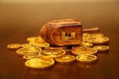 Monedas del gelt del oro del dreidel de Jánuca en una tabla imagen de archivo