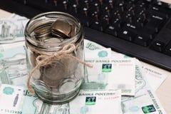 Monedas del metal en un tarro de cristal contra un fondo de las denominaciones de papel de mil rublos en la tabla cerca del tecla imagen de archivo libre de regalías