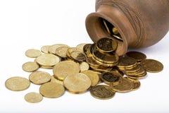 Monedas derramadas de un pote Imagenes de archivo