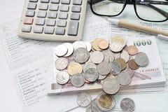 Monedas, dinero, calculadora, vidrios y pluma en libreta de banco del cuenta de ahorros Fotografía de archivo